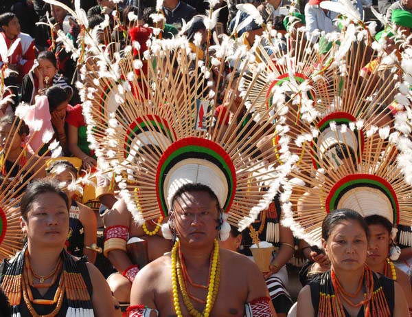 Tribal Angami Nagas with traditional attire looks on as they wait to perform during the first day of the annual celebration of Hornbill Festival at Kisama,Nagaland,India.  December 02  2008