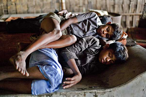 Using metal sheets for beds, workers sleep in crowded huts with no toilets.