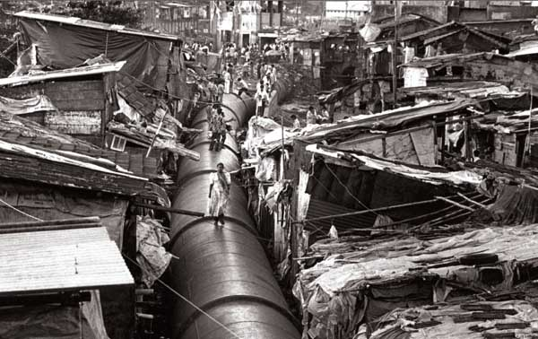 A PIPELINE carrying drinking water to more prosperous districts of India's largest city, Mumbai (population 20 million), passes through the shantytown of Mahim, where it serves as an impromptu thoroughfare. Photography by Sebastião Salgado.