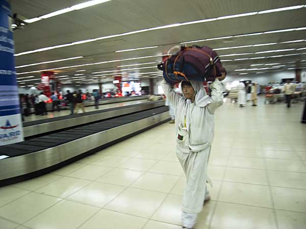 With thousands of Hajis all returning at the same time. Zia International Airport ran out of trolleys. A passenger takes matters in her own hand. 15th December. Zia International Airport. Dhaka. Bangladesh. Shahidul Alam/Drik/Majority World