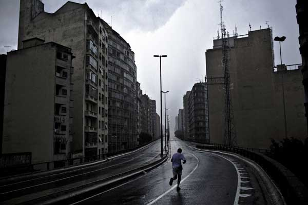 "A lonelu jogger runs through Sao Paulo's infamous ""Miocao"" highway which stretches through various residential areas in the center of the city. The construction of the urban pass highly devaluated the residential areas alongside it, has nurtured a variety of habitats for the homeless underneath it and has done little to resolve the ongoing traffic surge over the following decades."