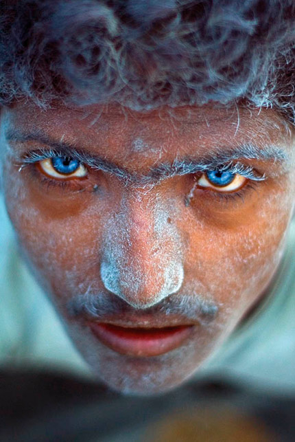 I shot this image at a stone quarry in Rampura, near Bangalore in India, while researching a story on the living and working conditions of labourers employed in the granite industry. I walked into the pit and came upon two boys operating a drill and planting dynamite sticks. Suddenly one of them looked up at me. His eyes were a startling blue and set like sapphires in his dust-covered face. I tried to ask him his name but he just stared and continued to drill. I though the roar of the machine had drowned out my voice, but then his friend told me that he was hearing impaired. The two boys had grown up in the quarry, because their parents worked there too. The constant exposure to high intensity blasts had damaged the blue-eyed boy's motor-neuron functions. I just had to click because I wanted to show this image to the world as a testimony to the dangers of child labour. Even though it was officially banned in India in 2006, child labour is still a huge problem. Sadly, I never did find out the boy's name.  Selvaprakash L. India