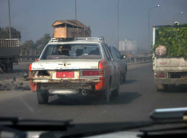 On my way to college, I pass the time in counting the coffins of violence in my Baghdad... in reading the black mourning banners hung on the wall of house and at the intersection of roads. It rarely happens now that Iraqis die in car accidents or from illness!! This family has put the coffin of their loved on the roof of a taxi. They received a death certificate from teh Al Kindi hospital and can have a proper burial... I thought 'how lucky this family is!'