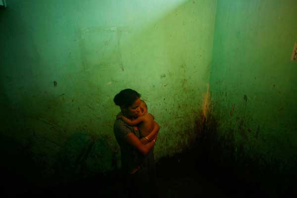 A sex worker with her baby. The men who have sired children here only rarely come back behind these curtains. October 2006.