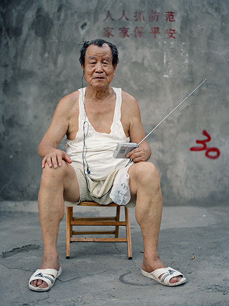 A portrait of an old Chinese man in his 50's or 60's, listening to the radio on the street.