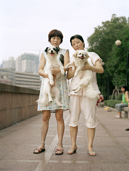 Two Chinese women in their pajamas hold up their dogs while taking them for a walk along the river in Shanghai. From what research shares, these two women are close friends and walk their dogs together every day.
