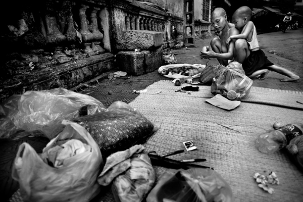 Mui, next to their sleeping area, goes through a bag of fruit she found in the street, sorting out the rotten pieces, while her son, Pha, leans on her for support. Mui, feeds herself and her son by picking through the garbage people leave on the street and taking out the food that is most edible. Hanoi. Vietnam. 1st March 2008 © Justin Maxon/Aurora Photos