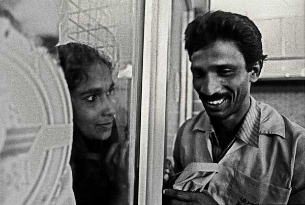 A woman bids farewell to her man, leaving for work in the middle east, from across the glass panels of Zia international Airport. Dhaka. Bangladesh. 1995. Shahidul Alam/Drik/Majority World