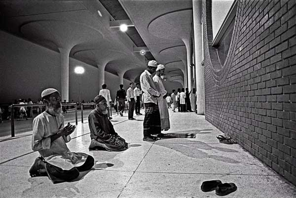 A migrant worker's family prays outside Zia International airport the night before he leaves. Dhaka, Bangladesh. 1995. Shahidul Alam