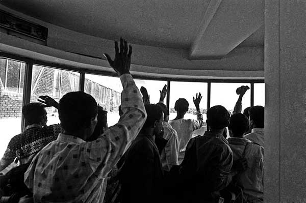 Abdul Malek and other migrant workers, waving goodbye to their family just before they board a plane bound for the Middle East, at Zia International airport, Dhaka, Bangladesh. Shahidul Alam