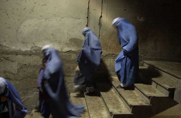 Burqa-clad Afghan women walk down stairs after they collected gifts from the U.S military ahead of the International Women's Day, in Kabul March, 04 2005. (AFP Photo/ Farzana Wahidy)