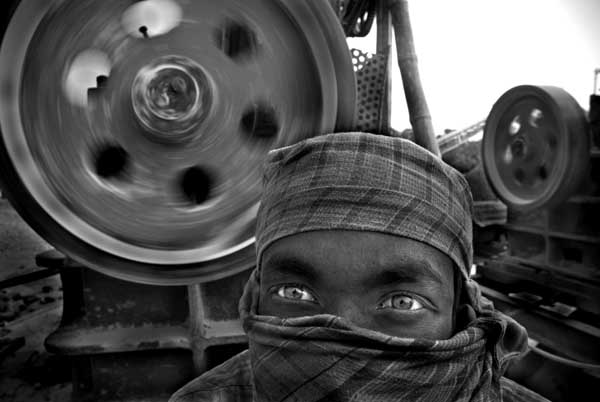 Kalam Ali (age 26) has been working at a stone crushing machine for last 4 years. He knows there are many risk in stone crushing. He covers his face using his gamchha (local weaved cloth), as an attempted safety measure from breathing in dust particles. Khaled Hasan