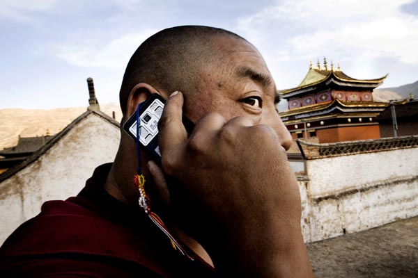 Monk speaking in cellphone inside the monastery in Tongren, which is located in one of the Tibetan-areas in China. Mads Nissen