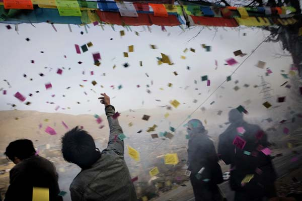 Crowd celebrating a religious Tibetan ceremony with prayers, fire crackers, confetti and flags in the city of Tongren. The ceremony was later infiltrated by undercover Chinese policemen. Mads Nissen