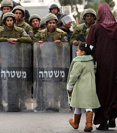 """A Palestinian girl and her mother walk near anti-riot Israeli police in Arab East Jerusalem on January 16, 2009. The Israeli army locked down the occupied West Bank today as Hamas called for a day of """"wrath"""" against the deadly offensive on Gaza. The West Bank will be closed off for 48 hours from midnight yesterday (2200 GMT), the army said in a statement. The announcement came after the Islamist movement Hamas called on Palestinians to observe a """"day of wrath"""" on Friday by staging anti-Israeli protests after the weekly Muslim prayers. PATRICK BAZ/AFP/Getty Images)"""